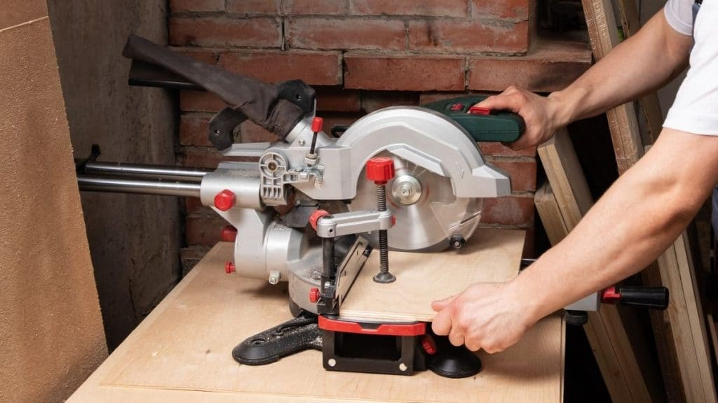 Carpenter cuts a piece of plywood with a miter saw.
