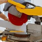 worker cuts baseboard wood on a miter saw before installing