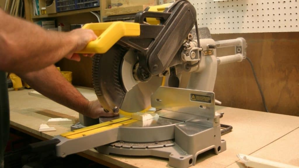 hand holding a sliding compound miter saw